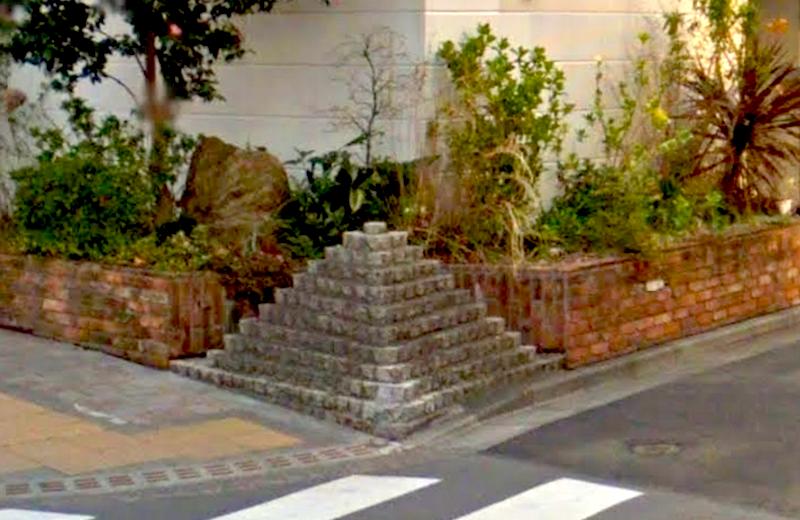 白いビルの角にあるピラミッドが曲がる目印